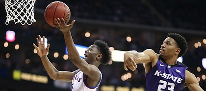 Kansas guard Marcus Garrett (0) goes to the bucket against Kansas State guard Amaad Wainright (23) during the second half, Friday, March 9, 2018 at Sprint Center in Kansas City, Mo.