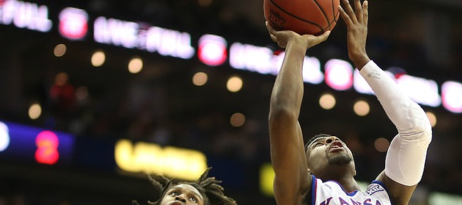 Kansas guard Malik Newman (14) gets in for a bucket past Kansas State guard Cartier Diarra (2) during the first half, Friday, March 9, 2018 at Sprint Center in Kansas City, Mo.