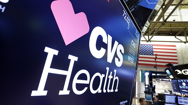 In this Dec. 4, 2017, file photo, the CVS Health logo appears above a trading post on the floor of the New York Stock Exchange. (AP Photo/Richard Drew, File)