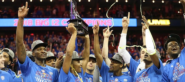 Kansas guard Devonte' Graham (4) hoists the Big 12 trophy following the JayhawksÕ 81-70 win over the Mountaineers in the championship game of the Big 12 Tournament, Saturday, March 10, 2018 at Sprint Center in Kansas City, Mo.