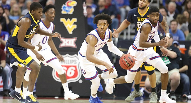 Kansas guard Devonte' Graham (4) pushes the ball up the court after coming away with a steal during the first half, Saturday, March 10, 2018 at Sprint Center in Kansas City, Mo.