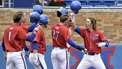 Kansas freshman Skyler Messinger, right, celebrates with his teammates Sunday, March 11, 2018, following a series sweep of St. John's.