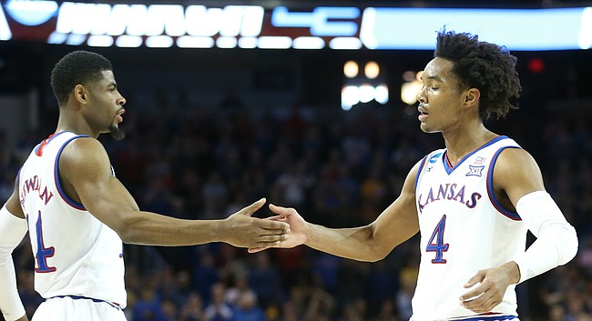 Kansas guard Malik Newman (14) and Kansas guard Devonte' Graham (4) slap hands after Graham was fouled on a three-point shot during the first half, Thursday, March 15, 2018 at Intrust Bank Arena in Wichita, Kan.