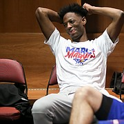 Kansas guard Marcus Garrett smiles as he listens to questions being asked of other players in the team locker room during a day of practices and press conferences at Intrust Bank Arena in Wichita, Kan.
