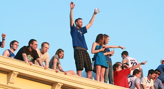 In this file photo from March 25, 2012, Kansas fans on Massachusetts Street take to rooftops after the Jayhawks defeated North Carolina to head to the Final Four.