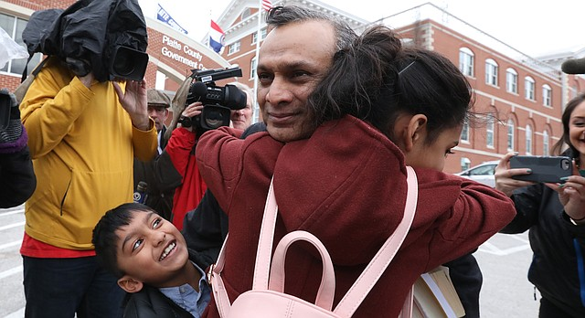Lawrence resident Syed Jamal hugs his children after he was released from the Platte County Jail, Tuesday, March 20, 2018, in Platte City, Mo.