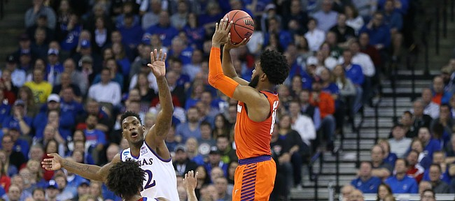 Clemson guard Gabe DeVoe (10) pulls up for a three against Kansas guard Devonte' Graham (4) and Kansas forward Silvio De Sousa (22) during the second half, Friday, March 23, 2018 at CenturyLink Center in Omaha, Neb.