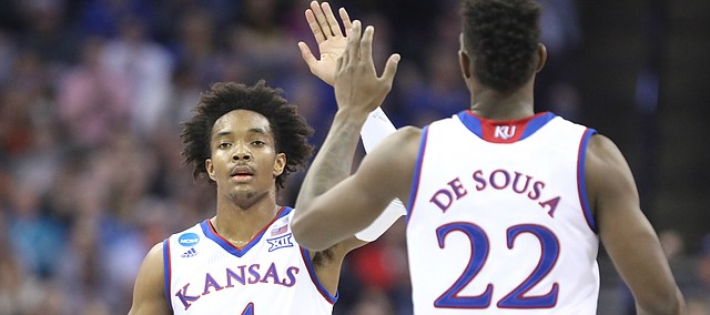 Kansas guard Devonte' Graham (4) and Kansas forward Silvio De Sousa (22) slap hands after connecting on a lob jam during the first half, Friday, March 23, 2018 at CenturyLink Center in Omaha, Neb.
