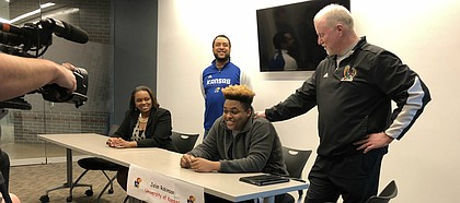 Jalan Robinson, joined by coach Bob Lisher, signs with KU football at a ceremony at Free State.