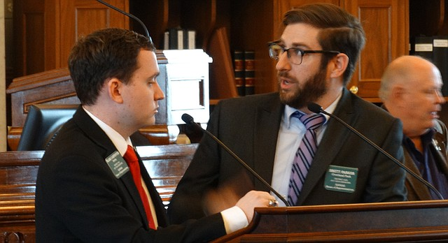 Rep. Blake Carpenter, left, R-Derby, questions Rep. Brett Parker, D-Overland Park, during debate on Parker's proposal to repeal a law that allows school districts to let teachers carry concealed firearms in classrooms, Tuesday, March 27, 2018, at the Kansas Statehouse in Topeka.