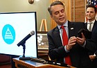 """During a March 29, 2018, news conference, Gov. Jeff Colyer demonstrates a new mobile app called """"iKan"""" that allows users to renew their vehicle registrations online. State officials said they also plan to expand uses of the app to provide access to other services like accessing birth certificates and registering to vote."""
