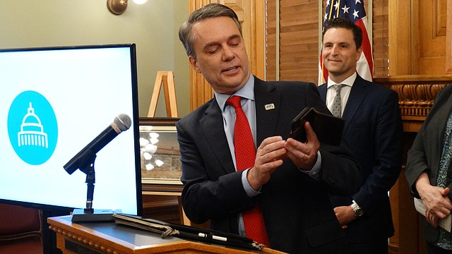 "During a March 29, 2018, news conference, Gov. Jeff Colyer demonstrates a new mobile app called ""iKan"" that allows users to renew their vehicle registrations online. State officials said they also plan to expand uses of the app to provide access to other services like accessing birth certificates and registering to vote."