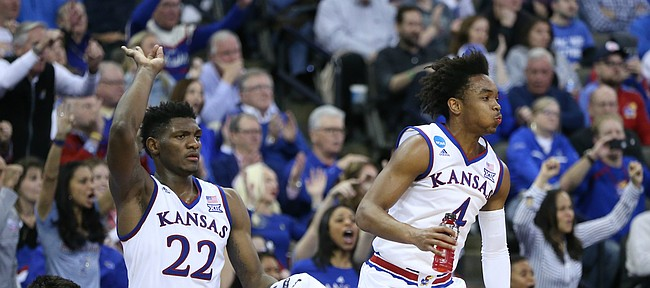 Kansas guard Devonte' Graham (4) leaps off the bench to celebrate a three with Kansas forward Silvio De Sousa (22) during the second half, Friday, March 23, 2018 at CenturyLink Center in Omaha, Neb.