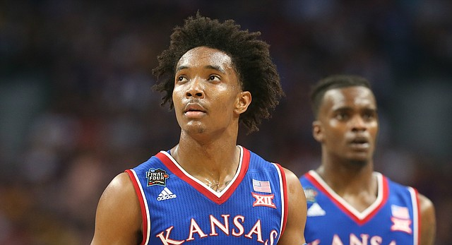 Kansas guard Devonte' Graham (4) looks at the scoreboard as he and Kansas guard Lagerald Vick (2) head to the bench during a timeout in the first half, Saturday, March 31, 2018 at the Alamodome in San Antonio, Texas.