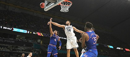Kansas guard Devonte' Graham (4) has a shot rejected by Villanova forward Omari Spellman (14) during the second half, Saturday, March 31, 2018 at the Alamodome in San Antonio, Texas.