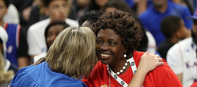 Florence Azuonuwu, mother of Kansas center Udoka Azubuike gets a welcoming hug from a KU fan prior to tipoff on Saturday, March 31, 2018 at the Alamodome in San Antonio, Texas.
