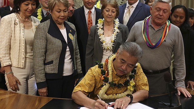 John Radcliffe, right, who was diagnosed with cancer in 2014, watches as Hawaii Gov. David Ige signs a bill to legalize medically assisted suicide on Thursday, April 5, 2018 in Honolulu. Radcliffe testified in favor of the measure and said Thursday he was happy it passed. Doctors in the state can now fulfill requests from terminally ill patients to prescribe life-ending medication. Hawaii is the sixth U.S. state, plus Washington, D.C., to legalize the practice. (AP Photo/Sophia Yan)