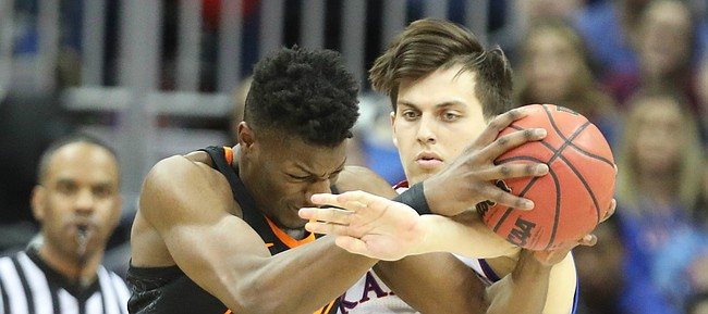 Kansas forward James Sosinski (55) tries to strip a ball from Oklahoma State forward Yankuba Sima (35) during the first half, Thursday, March 8, 2018 at Sprint Center in Kansas City, Mo.