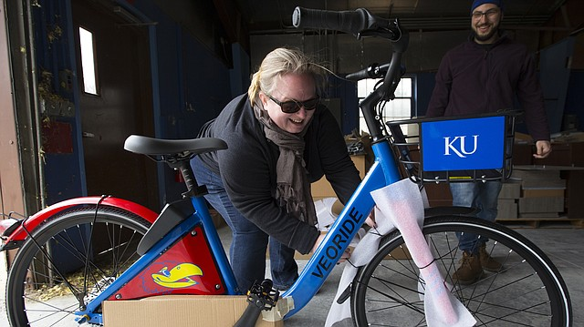 Margretta de Vries, transit analyst for KU Parking and Transit, excitedly pulls the wrapping from the first of 180 KU bike-share bicycles on Monday, April 9, 2018 at a storage facility near Bob Billings Parkway and Iowa Street, as Can Dai, a representative of bike-share company VeoRide stands by. A launch party for the program will take place from 10 a.m. to 2 p.m. Wednesday, April 18, on the lawn of Stauffer-Flint Hall.