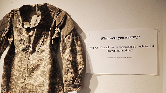 "A set of Army fatigues hangs on the wall for the ""What Were You Wearing? Survivor Art Installation"" on display in the Kansas Union gallery on the University of Kansas campus. The display, facilitated by KU's Sexual Assault Prevention and Education Center, is back by popular demand this month after its original KU debut last fall."