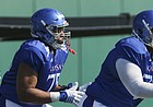 Kansas offensive lineman Andru Tovi, right, Antoine Frazier and Beau Lawrence shuffle through a line of pads during practice on Tuesday, April 10, 2018.