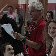Lawrence High swimmer Kendra Yergey, middle, smiles while LHS coach Kent McDonald says a few words about her during a senior night ceremony at the Lawrence Invitational on Tuesday. Yergey was recognized along with Shikeyah Brunello, right, and Chisato Kimura, who was not able to attend the meet because of a college visit. The Lions won their home meet.