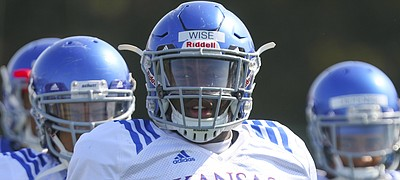 Kansas defensive tackle Daniel Wise and other members of the defense watch over a drill during practice on Tuesday, April 10, 2018.