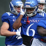 Kansas wide receiver Steven Sims Jr. (11) hits a pad as he runs through a drill during practice on Tuesday, April 17, 2018.
