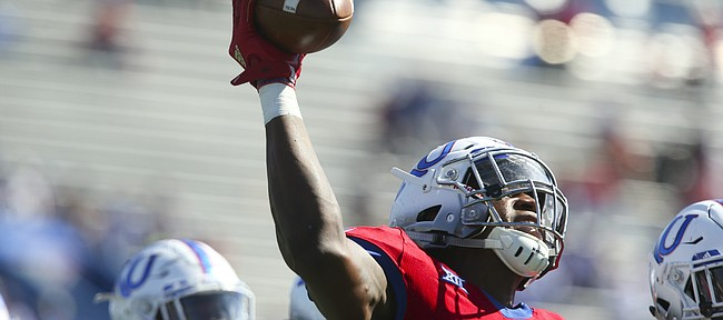Kansas defensive end Dorance Armstrong Jr. (2) hoists up the ball after recovering a fumble during the third quarter on Saturday, Oct. 7, 2017 at Memorial Stadium.