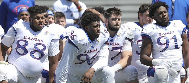 Kansas defensive tackle J.J. Holmes (88), Kansas defensive tackle Daniel Wise (96), Kansas defensive end Jelani Arnold (91) and others kneel to listen to Kansas head coach David Beaty following an open practice on Saturday, April 28, 2018 at Memorial Stadium.