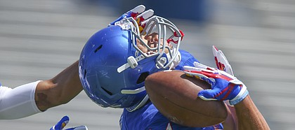 Kansas wide receiver Kerr Johnson Jr. (14) hangs on to a deep catch on his shoulder pad as cornerback Corione Harris reaches for him during an open practice on Saturday, April 28, 2018 at Memorial Stadium.