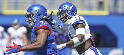 Kansas safety Mike Lee (11) smiles as he chases Kansas running back Kendall Morris (28) during an open practice on Saturday, April 28, 2018 at Memorial Stadium.