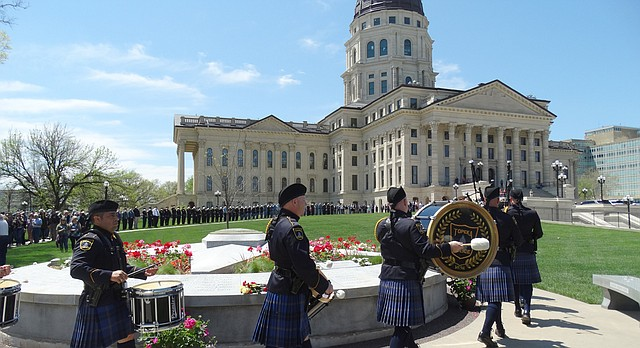 A pipe and drum corps marches past the Kansas Law Enforcement Memorial on Friday, May 5, 2018 during the 36th annual memorial service honoring peace officers who have been killed in the line of duty. Four new names were added to the memorial this year after researchers uncovered deaths that occurred in the late 19th and early 20th centuries.