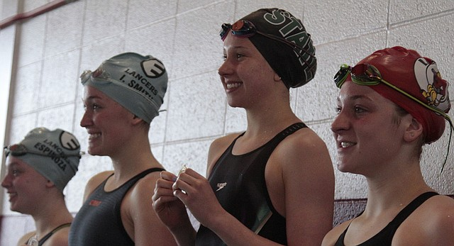 Free State senior Claire Campbell, second from right, stands atop the awards podium after breaking her own Sunflower League record in the 200-yard freestyle at the Sunflower League swim and dive meet on Saturday at Lawrence High. Campbell clocked in with a first-place time of 1:51.37. Lawrence High junior Morgan Jones, right, took third.