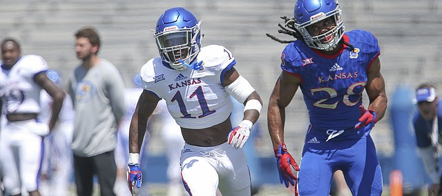 Kansas safety Mike Lee (11) keeps pace with Kansas running back Kendall Morris (28) as Morris runs a route during an open practice on Saturday, April 28, 2018 at Memorial Stadium.