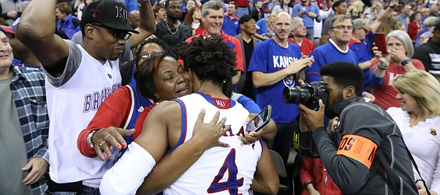 Kansas guard Devonte' Graham (4) hugs his mother as the Jayhawks celebrate a trip to the Final Four following their 85-81 overtime victory over Duke on Sunday in Omaha, Neb.