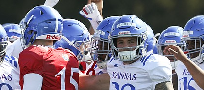 Kansas linebacker Joe Dineen (29) and other players gather in for a huddle during practice on Tuesday, April 10, 2018.