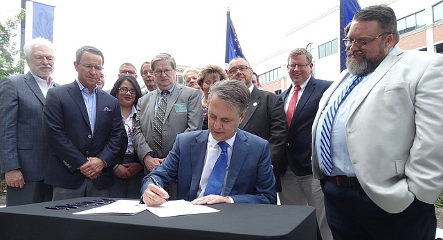 Gov. Jeff Colyer signs a liquor bill into law that will, among other things, allow Kansas establishments to open as early as 6 a.m., and let them serve beer through automated, self-service taps.
