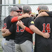 Lawrence High baseball head coach Brad Stoll, left, talks with his senior players after the Lions lost 1-0 to Olathe South in regional baseball game Wednesday, May 16, 2018 at College Boulevard Activity Center in Olathe.