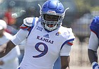 Kansas linebacker Kyron Johnson (9) runs in as safety Bryce Torneden (11) brings down running back Kezelee Flomo during an open practice on Saturday, April 28, 2018 at Memorial Stadium. Also pictured is Kansas offensive lineman Clyde McCauley III.