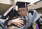 Haskell Indian Nations University graduates Bry Smiley, Navajo, Coyote Canyon, N.M., and Kristen Torres, Delaware, Kiowa and Comanche tribes of Oklahoma, Oklahoma City, hug following the 2018 commencement ceremony on Friday, May 18, 2018, at the Coffin Sports Complex.