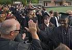Lawrence High graduate Ekow Boye-Doe high fives head baseball coach Brad Stoll as he and his fellow graduating seniors make their way through a gauntlet of well-wishing faculty members during the 2018 commencement ceremony on Wednesday, May 23, 2018 at LHS.