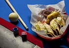The tacos at Crimson & Brews, 925 Iowa St., consist of seasoned ground beef, potatoes and a slice of American cheese fried in a corn tortilla and then topped with lettuce and powdered white cheddar.