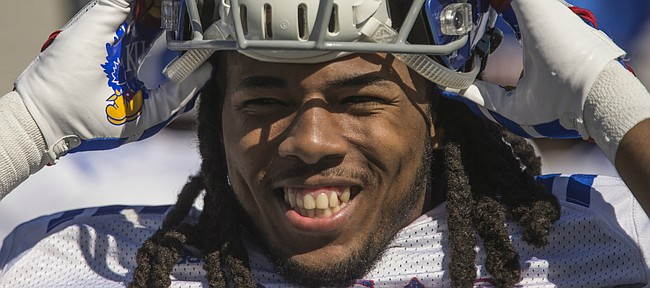 Kansas freshman cornerback Corione Harris smiles as he pulls on his helmet during practice on Monday, April 23, 2018.
