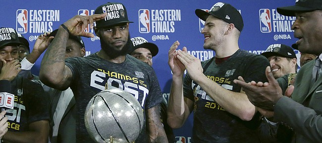 Cleveland Cavaliers forward LeBron James salutes after his team was presented the trophy for beating the Boston Celtics 87-79 in Game 7 of the NBA basketball Eastern Conference finals, Sunday, May 27, 2018, in Boston. (AP Photo/Elise Amendola)