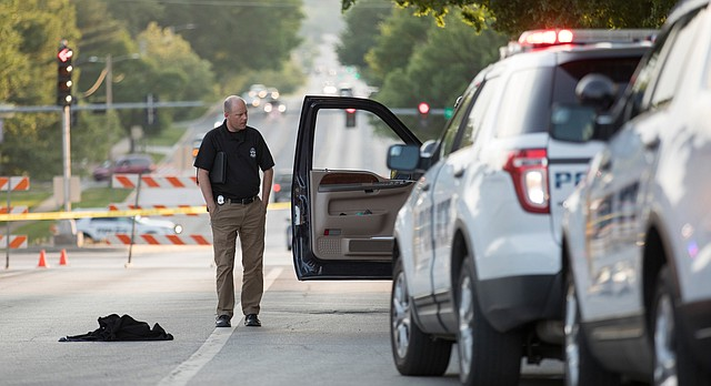 A detective with the Johnson County Sheriff's office walks around a Ford  Excursion that was driven