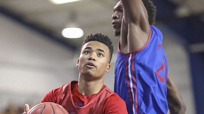 Red Team guard Devon Dotson dips under Blue Team forward Silvio De Sousa for a bucket during a scrimmage on Wednesday, June 13, 2018, at the Horejsi Family Athletics Center.