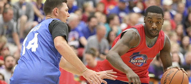 Red Team guard Elijah Johnson drives against Blue Team guard Tyrel Reed during the Rock Chalk Roundball Classic on Thursday, June 14, 2018 at Free State High School.