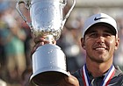 Brooks Koepka holds up the Golf Champion Trophy after winning the U.S. Open Golf Championship on Sunday in Southampton, N.Y.