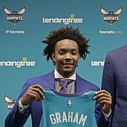 Charlotte Hornets draft picks Devonte' Graham, left, and Miles Bridges, right, pose for a photo with general manager Mitch Kupchak during a news conference for the NBA basketball team in Charlotte, N.C., Friday, June 22, 2018.